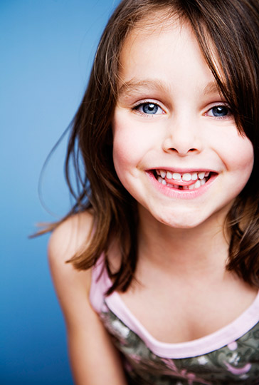A smiling little girl who is smiling happily. Our Naperville family dentistry practice is happy to provide dental services for your children!